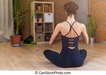 Back view of woman sitting in yoga lotus pose relaxing and meditating in living room