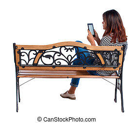 back view of woman sitting on bench and looks at the screen the tablet.