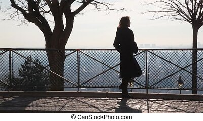 back view of woman stands near railing on Montmartre hill and looks at Paris
