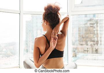 Back view of woman stretching hands before training
