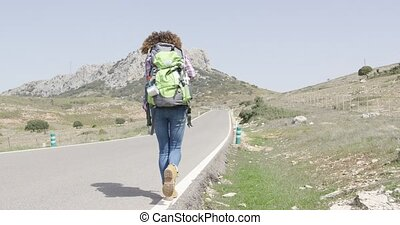 Back view of woman walking down road