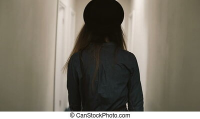 Back view of woman walking through corridor, come in room...