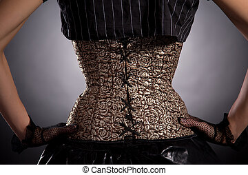 Back view of woman wearing golden corset