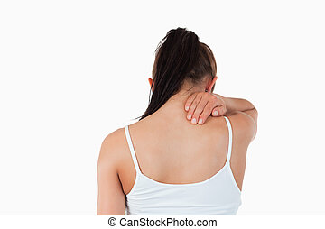 Back view of woman with pain in her neck against a white...