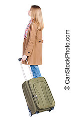 Back view of woman with suitcase looking up.