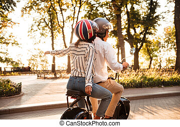 Back view of young african couple rides on modern motorbike