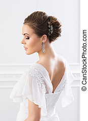 Back view of young and beautiful bride in white dress posing...