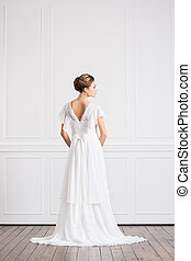 Back view of young and beautiful bride in white dress
