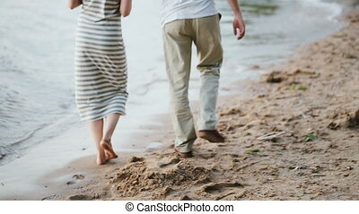 Back view of young attractive couple walking on the shore of the lake in evening on sunset. Man and woman on the beach.