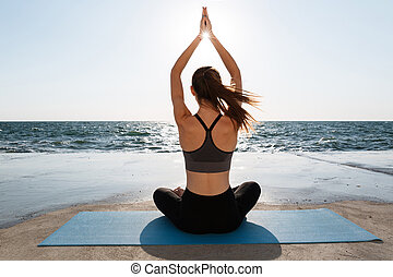 Back view of young attractive girl practicing yoga sitting ...