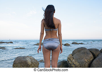 Back view of young beautiful Asian woman standing on the rocks o