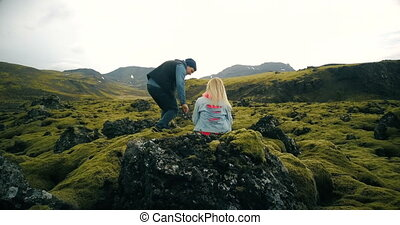 Back view of young beautiful couple sitting on the rock and enjoying the scenic landscape of the lava fields in Iceland.