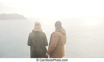 Back view of young beautiful couple standing on the shore of the sea and enjoying the view, turning and going away.