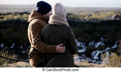 Back view of young beautiful couple stranding on the cliff near the Barnafoss waterfall in Iceland and enjoying the view