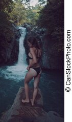 Back view of young beautiful tourist visiting the Aling-Aling waterfall of the Bali island, Indonesia - video in slow motion