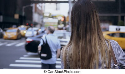 Back view of young beautiful woman crossing the road in New...