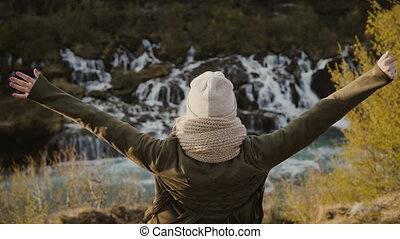 Back view of young beautiful woman standing near the waterfall and raising hands up, feeling freedom and happy.