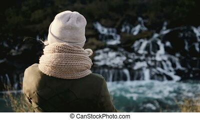 Back view of young beautiful woman standing near the Barnafoss waterfall in Iceland and enjoying the scenic landscape.
