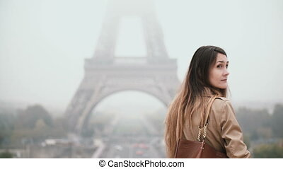 Back view of young beautiful woman walking in downtown of Paris, France near the Eiffel tower, exploring the city center