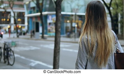 Back view of young beautiful woman with bag walking in the street. Female going to work. Slow motion.