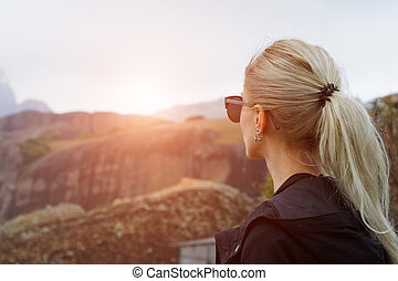 Back view of young blonde girl in mountains at sunset.