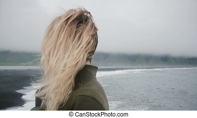 Back view of young blonde woman on the shore of the black...