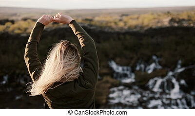 Back view of young blonde woman standing near the Barnafoss waterfall in Iceland and enjoying the beautiful landscape.