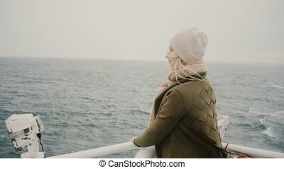 Back view of young blonde woman standing on the ship and...