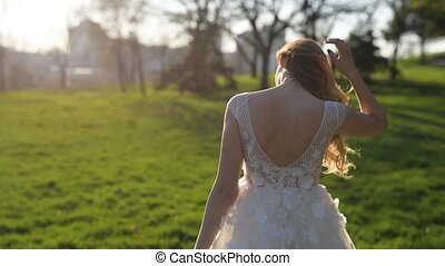 Back view of young bride at sunset in park.