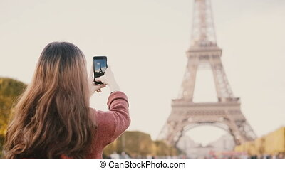 Back view of young brunette female taking photos of Eiffel tower on smartphone. Teenager exploring Paris, France.