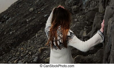 Back view of young brunette woman in lopapeysa walking...