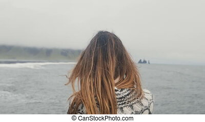 Back view of young brunette woman standing on the black beach and enjoying beautiful view of troll toes rocks in Iceland