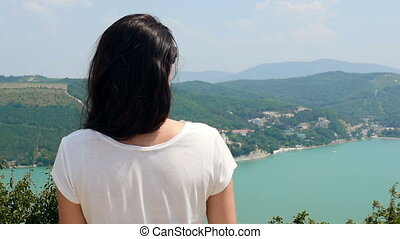 Back View of Young Brunette Woman Standing In Front of Mounatain Lake With Azure Water