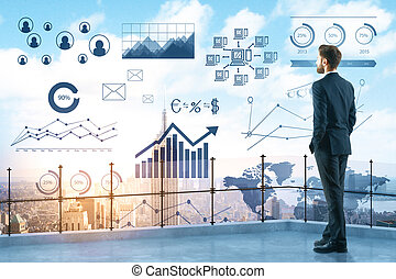 Back view of young businessman on balcony or rooftop looking at city with digital business charts. Economy concept. Double exposure