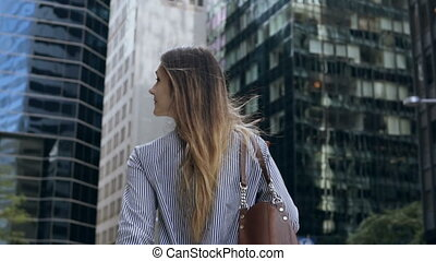 Back view of young businesswoman holding the documents and going to office building in New York, USA. Slow motion.