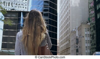 Back view of young businesswoman talk on mobile phone and...