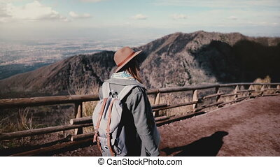 Back view of young cheerful tourist girl with camera hiking down from Vesuvius volcano turning around and smiling. Happy excited traveler female student enjoying amazing vacation day in Italy.
