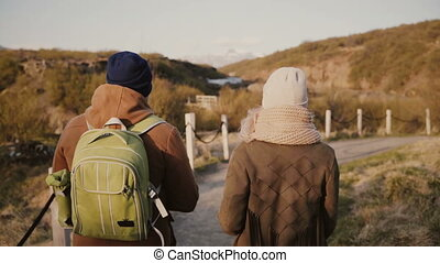 Back view of young couple have a romantic date on nature. Traveling man and woman hiking in mountains valley,