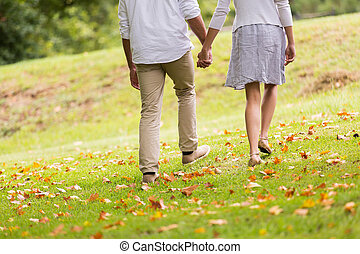 young couple holding hands walking in park