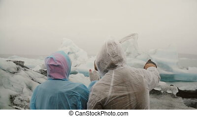 Back view of young couple in raincoats standing in ice...