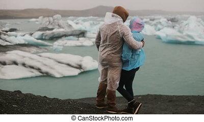 Back view of young couple in raincoats standing on the shore and looking on glaciers, icebergs in Iceland.