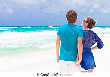 Back view of young couple on tropical beach in Tulum Mexico
