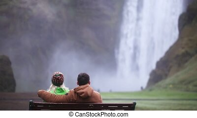 Back view of young couple sitting on the bench and enjoying the beautiful view of Skogafoss waterfall in Iceland.
