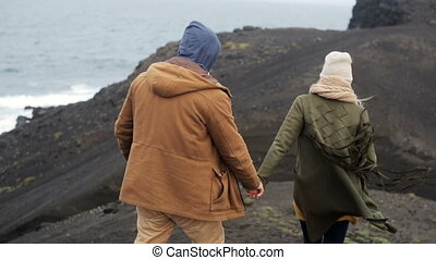 Back view of young couple walking on the cliffs near the sea in windy day, holding hands on romantic date on nature.