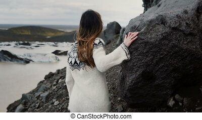 Back view of young explorer woman walking through the rocks in mountains, near the Vatnajokull ice lagoon in Iceland.