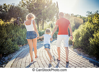 Back view of young family walking on park