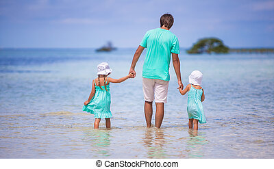 Back view of young father and his two little kids walking by the sea