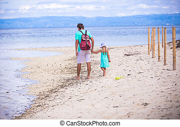 Back view of young father and little girl walking by the sea