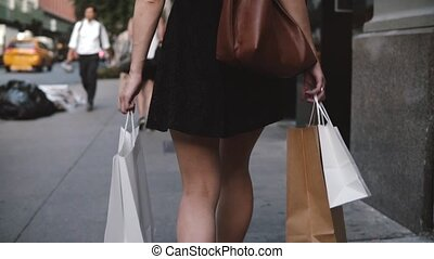 Back view of young female fashion blogger carrying shopping bags in both hands walking along the street slow motion. Successful European local girl enjoying impulsive buyings and consumerism.