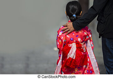 Back View of Young Female Geisha in Traditional Clothing Walking with Father in Kyoto, Japan.